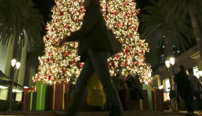 In this Thursday, Dec. 20, 2012, photo, a holiday shopper walks past a large Christmas tree at Fashion Island shopping center in Newport Beach, Calif. Holiday shopping, strong auto sale