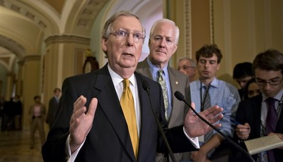 Senate Minority Leader Mitch McConnell of Ky., left, accompanied by Senate Minority Whip John Cornyn of Texas, gestures as he speaks with reporters on immigration, intelligence leaks an