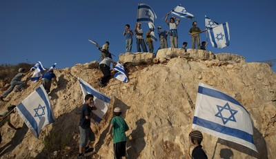 File - In this Sept. 20, 2011file photo, Israeli settler youths wave Israeli flags at the start of a protest march against Palestinian statehood, from the West Bank Jewish settlement of