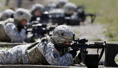 FILE - In this Sept. 18, 2012 file photo, female soldiers from 1st Brigade Combat Team, 101st Airborne Division train on a firing range while testing new body armor in Fort Campbell, Ky