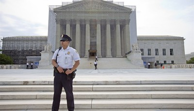 A police officer keeps watch outside the Supreme Court in Washington, Monday, June 17, 2013. With a week remaining in the current Supreme Court term, several major cases are still outst
