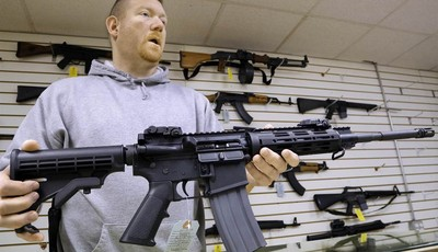 This Jan. 16 file photo shows John Jackson, co-owner of Capitol City Arms Supply, with an AR-15 rifle for sale at his business in Springfield, Ill.  From Oregon to Mississippi, Presiden