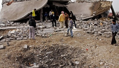 FILE - in this file photo taken on  Dec. 17, 2012 People inspect the scene of a car bomb attack in al-Mouafaqiyah, a village inhabited by families from the Shabak ethnic group, near the