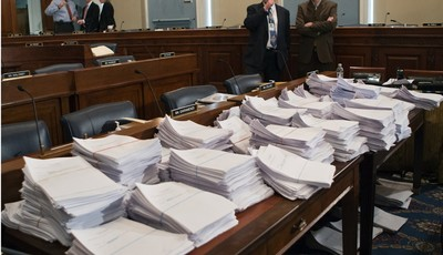 FILE - This May 15, 2013 file photo shows stacks of paperwork awaiting members of the House Agriculture Committee on Capitol Hill in Washington, Wednesday, May 15, 2013, as it meets to