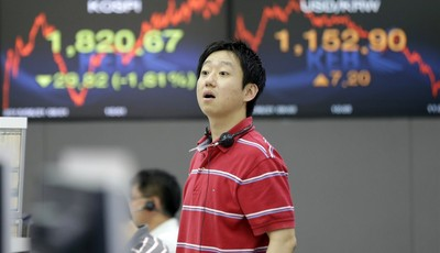 A currency trader asks a question to his colleague near a screen showing the Korea Composite Stock Price Index (KOSPI), left, and foreign exchange rate at the foreign exchange dealing r