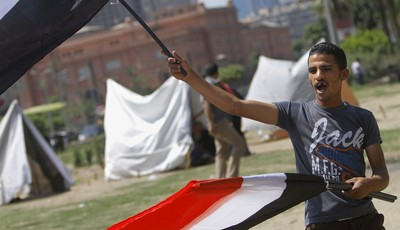 An Egyptian flag vendor waves flags in front of new erected strike tents in Tahrir Square, the focal point of Egyptian uprising in Cairo, Egypt, Saturday, June 22, 2013. Egypt