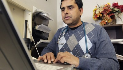 In this Thursday, March 28, 2013 photo, Dr. Damodar Poudel works on patient records at Family Healthcare Inc., in Chillicothe, Ohio. A shortage of primary care physicians in parts of th