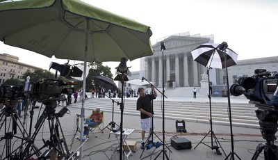 TV crews wait outside the Supreme Court in Washington as key decisions are expected to be announced Monday, June 24, 2013. At the end of the court