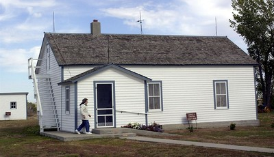 FILE - In this Oct. 10, 2002, file photo Edna Schwab walks toward the front door of the Lawrence Welk farm house in Strasburg, N.D., where Welk taught himself to play accordion. The Sta