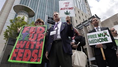 FILE - This May 6, 2013 file photo shows medical marijuana demonstrators holding up signs outside of the Federal Courthouse in Sacramento, Calif. The California Supreme Court ruled that