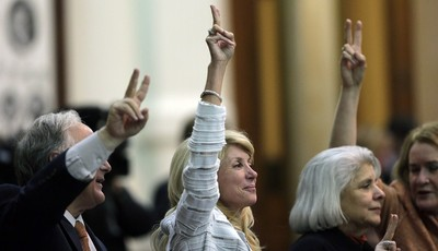 """FILE -  In this Tuesday, June 25, 2013, file photo, Sen. Wendy Davis, D-Fort Worth, center, holds up two fingers to signal a """"No"""" vote as the session where tshe tried to filibuster an a"""
