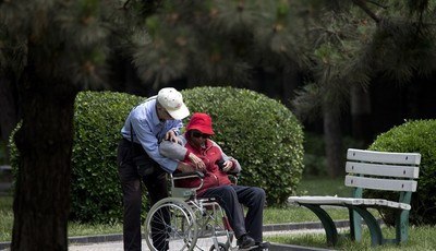 In this Thursday, May 23, 2013 photo, an elderly man helps his wife on a wheelchair at a park in Beijing. New wording in the law requiring people to visit or keep in touch with their el