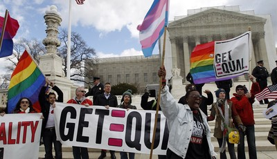 FILE - In this March 27, 2013 file photo, demonstrators hold flags and chant in front of the Supreme Court in Washington on the second day of gay marriage cases before the court. The Su