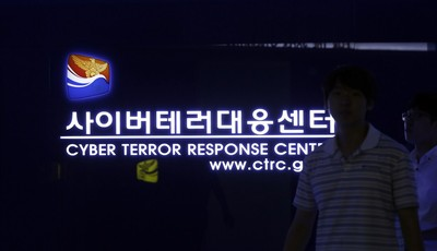 In this Friday, July 5, 2013 photo, a man walks by a sign at Cyber Terror Response Center of National Police Agency in Seoul, South Korea. The hackers who knocked out tens of thousands