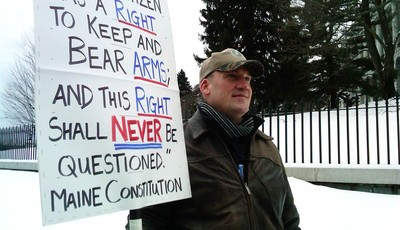 Michael Hein of Augusta, Maine, holds a sign in front of the Maine State house during a Gun Appreciation Day rally, Saturday, Jan. 19, 2013.  Rallies are being held by gun rights advoca