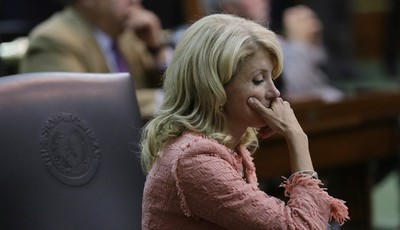 Sen. Wendy Davis, D-FortWorth, sits at her desk after the Texas Senate passes an abortion bill, Friday, July 12, 2013, in Austin, Texas. The bill will require doctors to have admitting