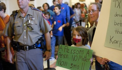 Linda Maska and Theresa Maska, 8, hold anti-abortion rights signs outside of the Senate Gallery in the State Capitol in Austin, Texas on Friday, July 12, 2013. The Texas Senate