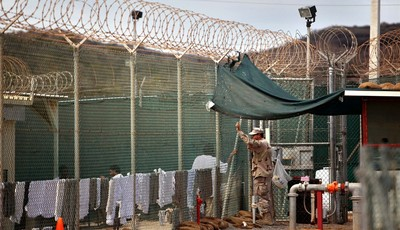 FILE - In this Jan. 21, 2009, file photo, reviewed by the U.S. Military, a guard talks to a Guantanamo detainee in the open yard in Camp 4 detention center on the U.S. Naval Base in Gua