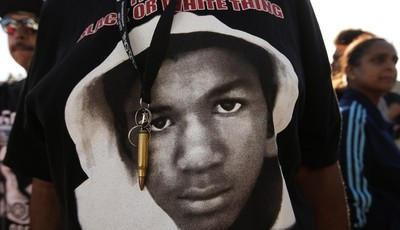 An image of Trayvon Martin and a bullet shell keychain hanging from a protester