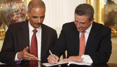 Puerto Rico's Governor Alejandro Garcia Padilla, right, signs an agreement as U.S. Attorney General Eric Holder gestures at the governor executive mansion in San Juan, Puerto Rico, Wedn