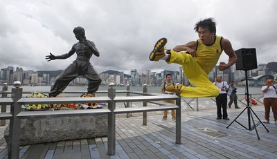 Chinese actor Mei Zhiyong dressing as the late Hong Kong Kung Fu star Bruce Lee performs in front of the bronze statue in Hong Kong Saturday, July 20, 2013 to commemorate the 40th anniv