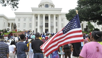 People gather  in front of the Alabama Capitol during a rally, Saturday, July 20, 2013, in Montgomery, Ala. The Rev. Al Sharpton
