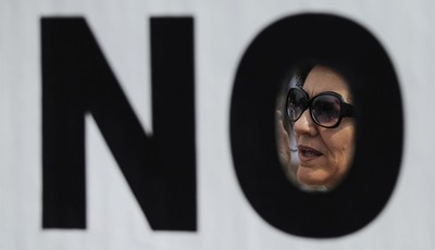A protestor is seen through a banner as she shouts slogans during a demonstration against government-imposed austerity measures and labor reforms in the public healthcare sector in Madr
