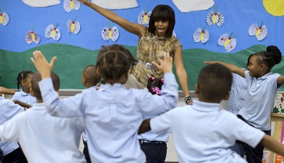 FILE - In this May 24, 2013 file photo, first lady Michelle Obama dances with a pre-Kindergarten class at Savoy Elementary School in Washington. The Savoy School was one of eight school