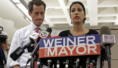 New York mayoral candidate Anthony Weiner, left, listens as his wife, Huma Abedin, speaks during a news conference at the Gay Men