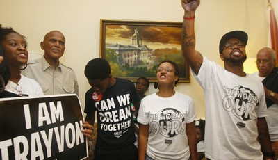 At left, American singer, songwriter, actor and social activist Harry Belafonte, Jr. listens as Dream Defenders Executive Director Phillip Agnew, right, raises his fist as he leads a ch