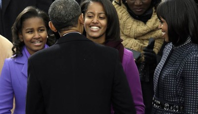 President Barack Obama greets his daughter Sasha and Malia as first lady Michelle Obama watches at the ceremonial swearing-in at the U.S. Capitol during the 57th Presidential Inaugurati