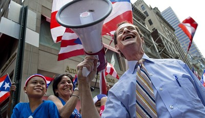 FILE - In this June 12, 2011 file photo, New York mayoral candidate Anthony Weiner smiles after sharing a megaphone as he greeted parade goers in the Puerto Rican Day Parade in New York