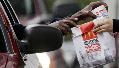 FILE - In this Jan. 22, 2010 file photo, a customer grabs lunch at a McDonalds drive-through in Chicago.  Fast-food chains such as McDonald's, Burger King and Wendy's are trumpeting pri