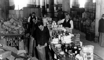 FILE - In this March 18, 1932, file photo workman sort individual 25-pound packages of unperishable food for needy families in New York City, where the The Emergency Unemployment Relief