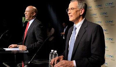 In this photo provided by NJTV, Newark Mayor Cory Booker and Rep. Rush Holt share a laugh before the U.S. Senate Democratic Primary debate televised on NJTV from Montclair State Univers