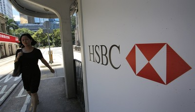 A woman walks past a logo of HSBC Holdings at a Hong Kong down town street Tuesday, Aug. 6, 2013. Asian stock markets were mostly lower Tuesday despite an upbeat report on U.S. service