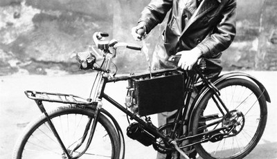 FILE - In a Oct. 25, 1940 file photo, F. Hans, mechanic of Frankfort-on-Main, tests the battery on an electrically driven bicycle device he has constructed to help save gasoline in the