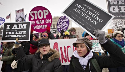Anti-abortion activists and supporters of legal abortion stand in front of the Supreme Court in Washington, Friday, Jan. 25, 2013, on the 40th anniversary of the Roe v. Wade decision.