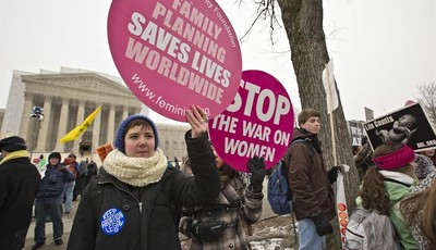 Abortion rights protesters hold signs as anti-abortion activists march past the Capitol to the Supreme Court in Washington, Friday, Jan. 25, 2013, as they observe the 40th anniversary o