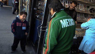 Mexican immigrant Roberto Garcia, center, and son Alan, left, look at wrist watches while shopping in Los Angeles, Monday, Jan. 28, 2013. Seeking swift action on immigration, President