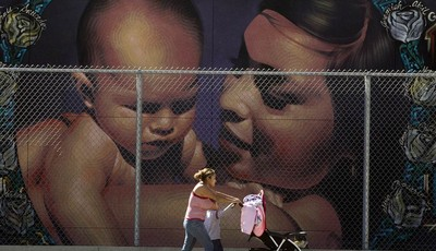 A mother walks with her children to the MacArthur Park Primary Center School in Los Angeles Thursday, Jan. 31, 2013. Within six months, California