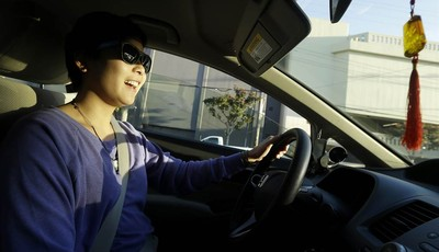 In this Jan. 4, 2013 photo, Lyft driver Nancy Tcheou smiles as she drives in San Francisco. Fed up with traditional taxis, city dwellers are tapping their smartphones to hitch rides fro
