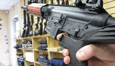 """In this Feb. 1, 2013 photo, an employee of North Raleigh Guns demonstrates how a """"bump"""" stock works at the Raleigh, N.C., shop. The accessory devices, which legally allow a semiautomati"""