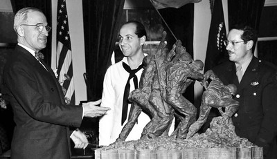 FILE - In this June 4, 1945 file photo, President Harry Truman, left, is presented with a bronze statue by sculptor Felix de Weldon, center, and Associated Press photographer Joe Rosent