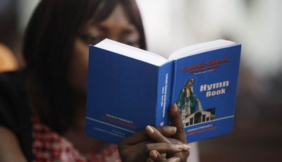 A lady studies a hymn book during an evening mass at a Catholic church in Lagos, Nigeria, Monday, Feb. 11, 2013.  In Africa, where the Catholic church continues to grow, worshippers and
