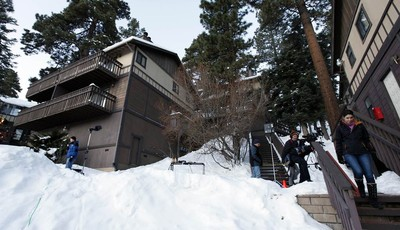 Members of the news media are shown outside a home, at left, in Big Bear, Calif., where two women were taken hostage by fugitive Christopher Dorner. Police scoured mountain peaks for da