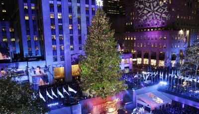 FILE - In this Wednesday, Nov. 28, 2012 file photo, the Rockefeller Center Christmas tree is lit during the 80th annual tree lighting ceremony at Rockefeller Center in New York. Comcast