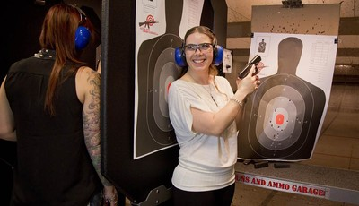 Tanya Morris, right, poses for a photo with her shot-up target after getting married at the Guns and Ammo Garage, Thursday, Feb. 14, 2013, in Las Vegas. Las Vegas is embracing tourists