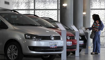 In this Feb. 1, 2013 photo, a couple looks at the price of a new vehicle that has already been sold, parked next to other already sold cars on display at a Volkswagen salesroom in Carac