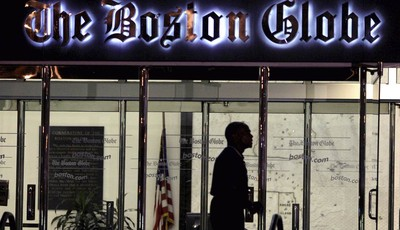 FILE - In this July 20, 2009 file photo, a security guard walks past the entrance of The Boston Globe building in the Dorchester neighborhood of Boston. The New York Times Company, whic